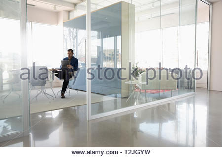 Businessman using digital tablet in modern conference room - Stock Image