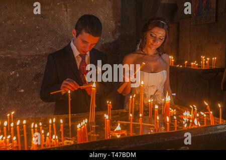 Armenia, Vagharshapat (Etchmiadzin), People lighting prayer candles at Etchmiadzin Holy See Cathedral, 301-303 AD, built by Armenia's patron saint Gre - Stock Image