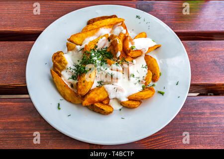 Fried potatoes with white milk sauce and dill - Stock Image