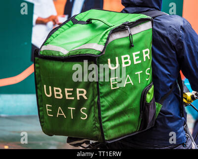 Uber Eats Courier in heavy rain in London - an Uber Eats Food Delivery Courier getting drenched in a heavy downpour - Stock Image