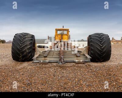 Bulldozer used as boat launcher parked on the shingle beach with buildings behind Aldeburgh Suffolk - Stock Image
