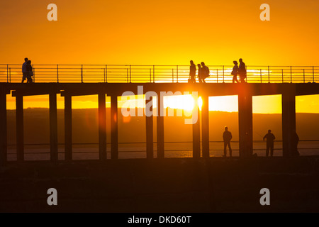 People walk along Whitby West Pier at sunset. - Stock Image
