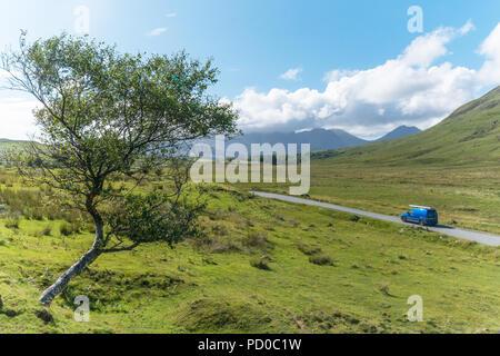 A car drives through the Scottish Highlands, Scotland, UK - Stock Image