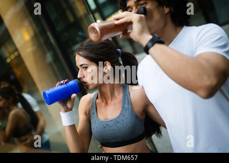 Young happy fitness friends running in urban area - Stock Image