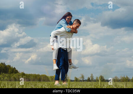 Couple of young beautiful man and woman having fun outdoors at sunny summer day. playing piggyback ride - Stock Image