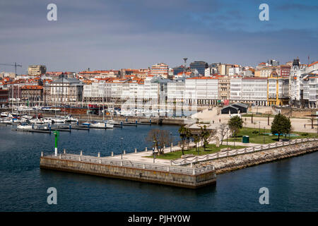 Spain, Galicia, A Coruna, harbour, waterfront park and marina by waterfront buildings with glazed facade - Stock Image