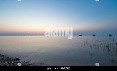 Sunset at the foggy lake - Stock Image