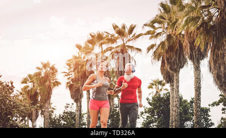 Happy fitness friends running at sunset outdoor - Couple of joggers training at evening time - Stock Image