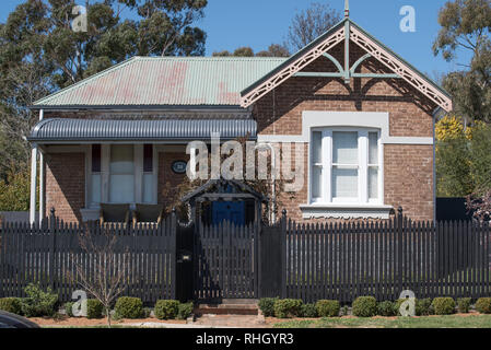 A Federation era brick and steel roofed home with a bull nose front veranda and fret work over the hip roof end in Millthorpe, New South Wales, Aust. - Stock Image
