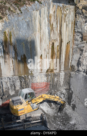 hammer drill excavator in construction site by a mountain wall, Italy - Stock Image