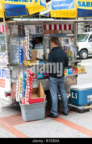 CHARLOTTE, NC, USA-10/30/18: A  man places an order at a small food cart on Tryon Street in uptown. - Stock Image