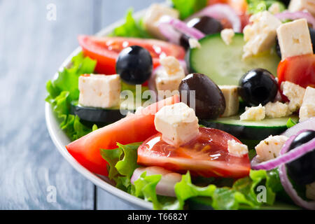 Fresh greek salad with tomato, lettuce, cucumber, purple onion, feta cheese and olives on a blue wooden table - Stock Image