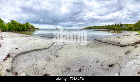 Streams of water flow into a small bay in this HDR image taken on the island of Islay in Scotland. - Stock Image