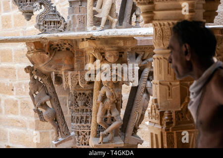 Holy man with carved stone figures in Chandraprabhu Jain Temple  jaisalmer, Rajasthan, India - Stock Image