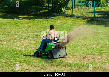 A man on a ride-on mower, cutting the grass without using a grass box and so throwing dust and stones into the air. - Stock Image