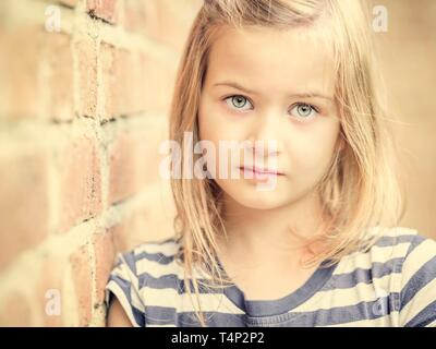 Girl, 10 years, leans against a wall, direct view, face, portrait, Germany - Stock Image