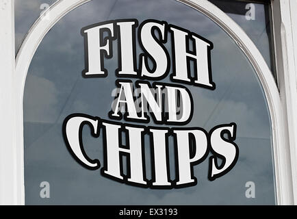 Fish and chips sign painted onto shop window to advertise the popular British Seaside delicacy to tourists - Stock Image