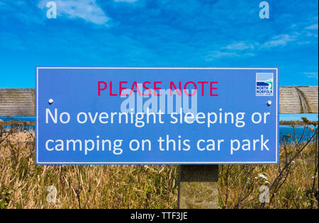 Sign attached to fence near Cromer beach: 'No overnight sleeping or camping on this carpark'. Erected by North Norfolk District Council. England, UK. - Stock Image