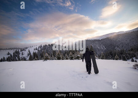 Rear view of man carrying ski while walking on snowy mountain - Stock Image