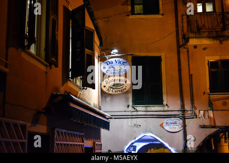 Late night in Monterosso Al Mare, Cinque Terre Italy with a colorful sign of violet and peach advertising an Italian - Stock Image