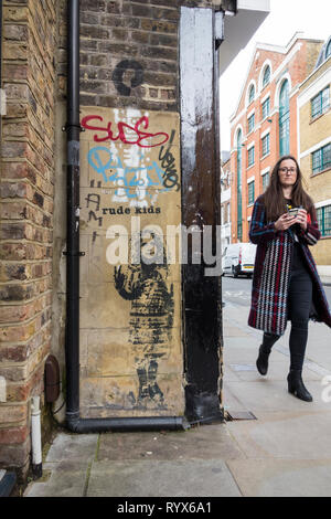 A woman walking past a piece of Rude Kids graffiti on a London street, UK - Stock Image