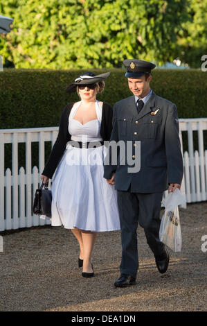 Chichester, West Sussex, UK. 14th Sep, 2013. Goodwood Revival. Goodwood Racing Circuit, West Sussex - Saturday 14th September. Two visitors to the festival dressed in an RAF uniform and period dress walk through the circuit. Credit:  MeonStock/Alamy Live News - Stock Image