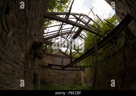 Derelict and overgrown mill buildings, Linthwaite, West Yorkshire - Stock Image
