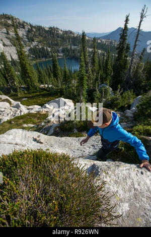 Photograph of a ten year old boy hiking in the mountains with a view of a lake in the background, Selkirk Mountains, Sandpoint, Idaho, USA - Stock Image
