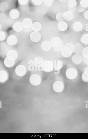 Abstract background of metallic black and white holiday bokeh lights with free space for text. - Stock Image