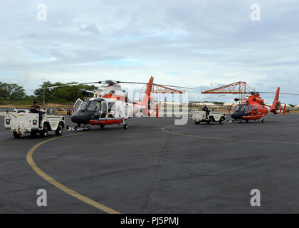 Air Station Barbers Point aircrews move two MH-65 Dolphin helicopters at Air Station Barbers Point, Hawaii, Aug. 25, 2018. The air station preparing the helicopters for tasking in the aftermath of Hurricane Lane. (U.S. Coast Guard photo by Petty Officer 3rd Class Matthew West/Released) - Stock Image