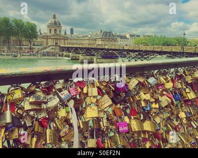 Pont des Arts or Passerelle des Arts, a pedestrian bridge in Paris, France with side panels covered in padlocks - Stock Image