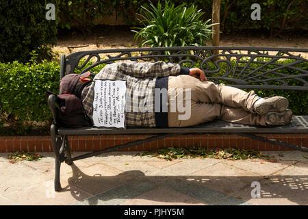 Spain, Jerez de La Frontera, Plaza de Abastos, homeless man sleeping on bench, with begging sign on back - Stock Image