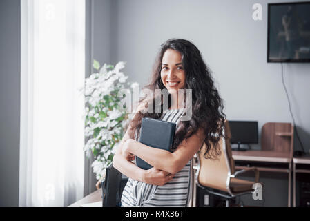 Beautiful smiling woman in office at work - Stock Image