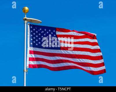 American flag in full sunlight, blowing in the wind with blue sky background, Castle Rock Colorado US. Photo taken in April. - Stock Image