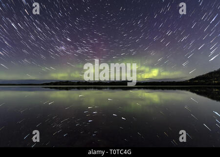 Star Trail and Aurora Australis or Southern Lights reflected in still water - Stock Image