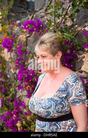woman posing among pink flowers leaning against stone wall - Stock Image