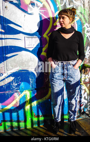 Sion, Switzerland, 23rd Dec 2017.  Woman in 8os vintage jeans pressed up against wall of graffiti. - Stock Image