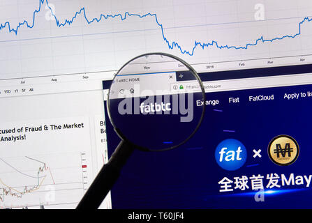 MONTREAL, CANADA - APRIL 26, 2019: Fatbtc cryptocurrency digital assets exchange logo and home page on a laptop screen under magnifying glass. - Stock Image