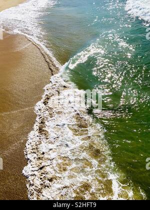 Overhead photo of a wave breaking on the shore. Manhattan Beach, California USA. - Stock Image