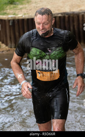 Male mud runner wearing a bra hopefully as a joke - Stock Image