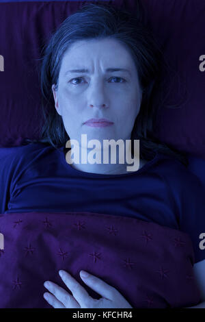 Middle aged woman lying awake in her bed at night, worrying because of an uncomfortable pressure in her chest and - Stock Image