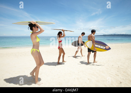 Friends walking with surfboards. - Stock Image