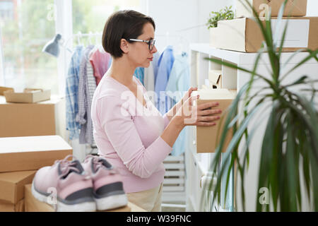 Manager of online shop putting packed order on shelf while working in warehouse - Stock Image