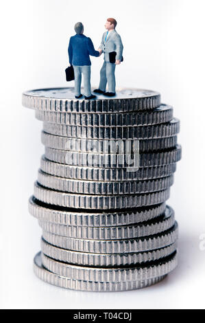 miniature figurines shaking hands on top of a stack of coins, financial deal concept - Stock Image