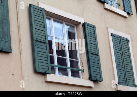 Details of old medieval style building. The building has beige concrete walls and the window frames are white and green and made of wood. - Stock Image