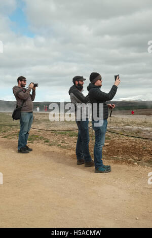Geysir, South Iceland: three men waiting for the geyser to erpt and take photographs - Stock Image