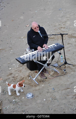 busker playing keyboards and singing on beach of the River Thames, Southbank, London, England, UK - Stock Image