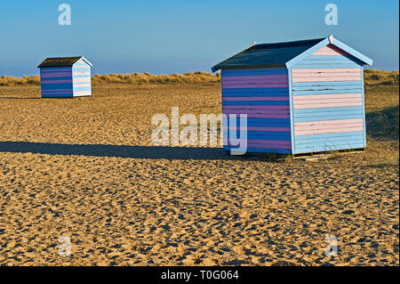 Traditional seaside beach huts in blue and pink stripes on the shingle coastal strip in Great Yarmouth, Norfolk - Stock Image