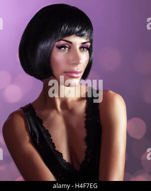 Portrait of a gorgeous woman with perfect hair and makeup over purple background, fashion retro style photo shoot - Stock Image