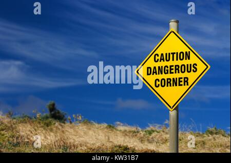 Yellow sign warning of dangerous corner against bright blue summer sky. - Stock Image